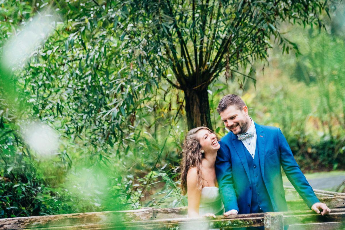 photographe mariage lille nord jeremy hourquin apres mariage photo rire fou couple pont arbre verdure.jpg